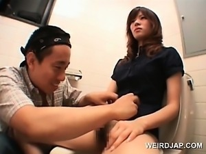 Asian teen cutie shows twat while pissing in a toilet