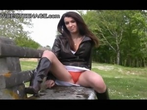 brunette teen Sarah shows her red panty during an upskirt in a public park