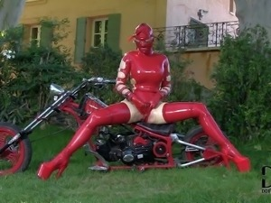 Latex Lucy is a kinky adult model. Masked lady poses in her red rubber outfit...