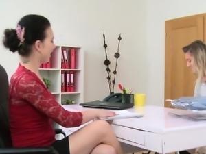 Brunette female agent eats sexy blonde in office