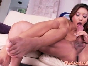 Asian babe footworshiped on the couch