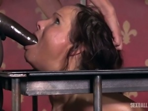 Beautiful and lean brunette with juicy breasts caged and facefucked with strapon