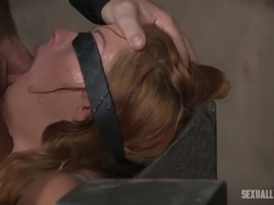 Lovely and hot blonde woman blindfolded and shackled to the wooden posts