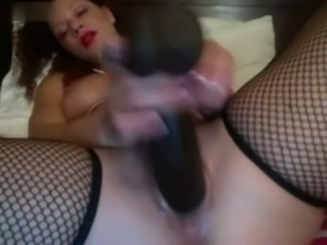 Dazzling babe in fishnet stockings poking her pussy with big sex toy