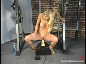 Nice blonde with hot tits gets toyed by a machine in a gym