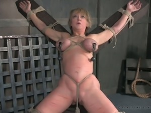 Busty short haired brunette bound to the wooden cross and suffocated