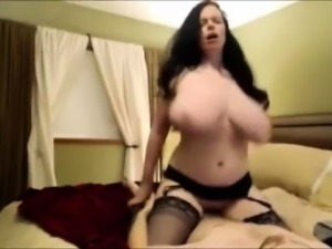 Big breasted brunette in stockings bounces on a stiff pole
