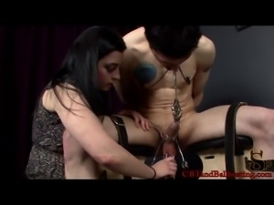 Beautiful dominatrix with long dark hair and a hot body torturing a stranger
